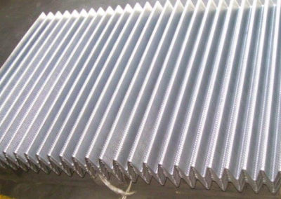Perforated sheet pressed to form a corrugation to be used as part of a filtration system